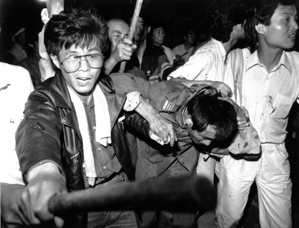 Участники демонстрации захватили водителя танка. Кое-кто из толпы избивает его. Фото сделано 4 июня 1989 в Пекине. (REUTERS/Stringer)