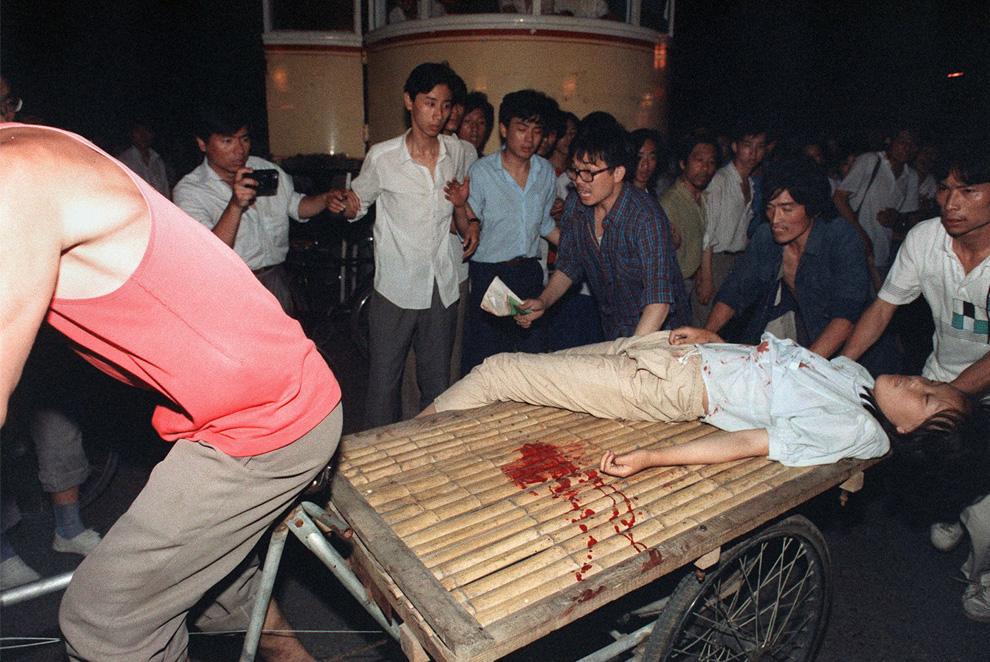 Девушку раненую во время столкновений между армией и студентами у площади Тяньаньмэнь увозят на тележке. Фото сделано 4 июня 1989 года. (MANUEL CENETA/AFP/Getty Images)