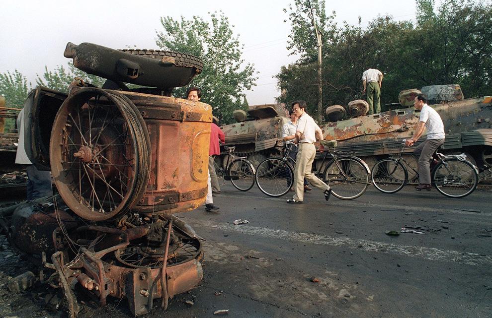 Жители Пекина проходят мимо сожженного военного транспорта. Всего  демонстранты сожгли более чем 20 бронетранспортеров и других транспортных средств, не пуская войска на площадь Тяньаньмэнь. Фото сделано 4 июня 1989 года. (MANUEL CENETA/AFP/Getty Images)