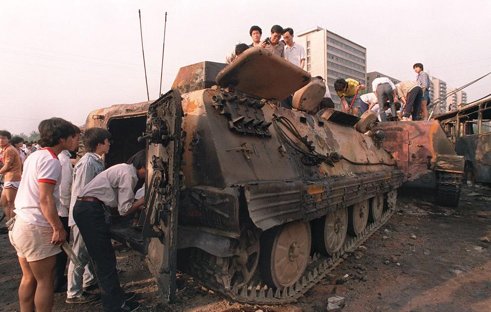На этом архивном фото, сделанном 4 июня 1989 года, жители Пекина заглядывают внутрь одного из бронетранспортеров, которые демонстранты сожгли, не пуская войска на площадь Тяньаньмэнь. (MANUEL CENETA/AFP/Getty Images)