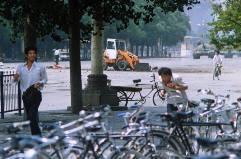 На этой фотографии, сделанной 5 июня 1989 года и впервые представленной информационным агентством AP в четверг, 4 июня 2009, три неопознанных человека убегают с площади Тяньаньмэнь, а еще один (на заднем плане слева) стоит, в одиночку блокируя приближающуюся колонную танков (на фоне справа). Это фото, сделанное Террилом Джонсом, который в 1989 был репортером AP, было представлено публике во время обсуждений в сети событий на площади Тяньаньмэнь в фотоблоге The New York Times Lens Blog. (AP Photo/Terril Jones)
