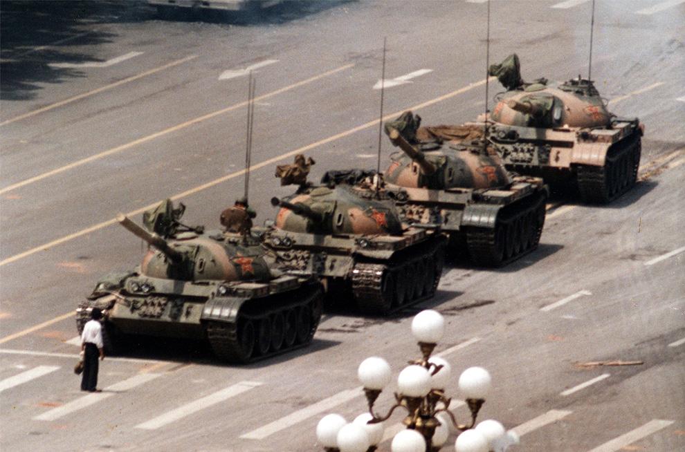 На этом архивном фото, сделанном 5 июня 1989, демонстрант блокирует колонну танков, двигающуюся в восточном направлении по авеню Чанган 5 июня 1989 года у отеля Пекин. Вскоре мужчину оттащили и танки продолжили свой путь. (AP Photo/ Jeff Widener)
