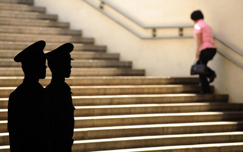 Силуэты сотрудников военизированной полиции наблюдающих за одним из входов на площадь Тяньаньмэнь 3 июня 2009. Накануне 20-й годовщины событий на площади китайская полиция ужесточила ограничения с целью предотвратить волнения. (PETER PARKS/AFP/Getty Images)