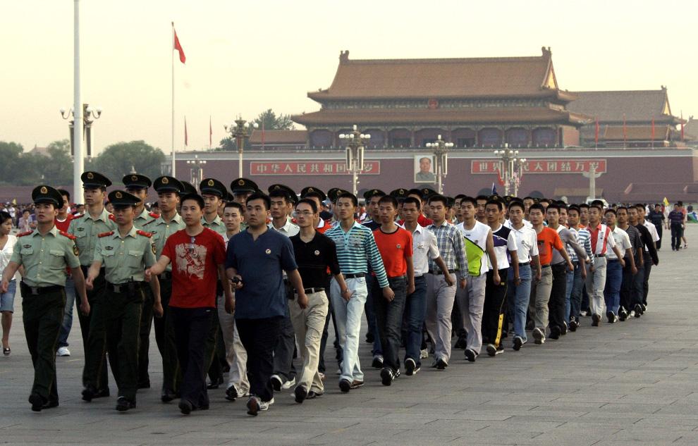 Военизированные полицейские, одетые в штатское и в форму, маршируют колонной после церемонии поднятия флага перед гигантским портретом председателя Мао Цзэдуна на площади Тяньаньмэнь 4 июня 2009. (REUTERS/ David Gray)