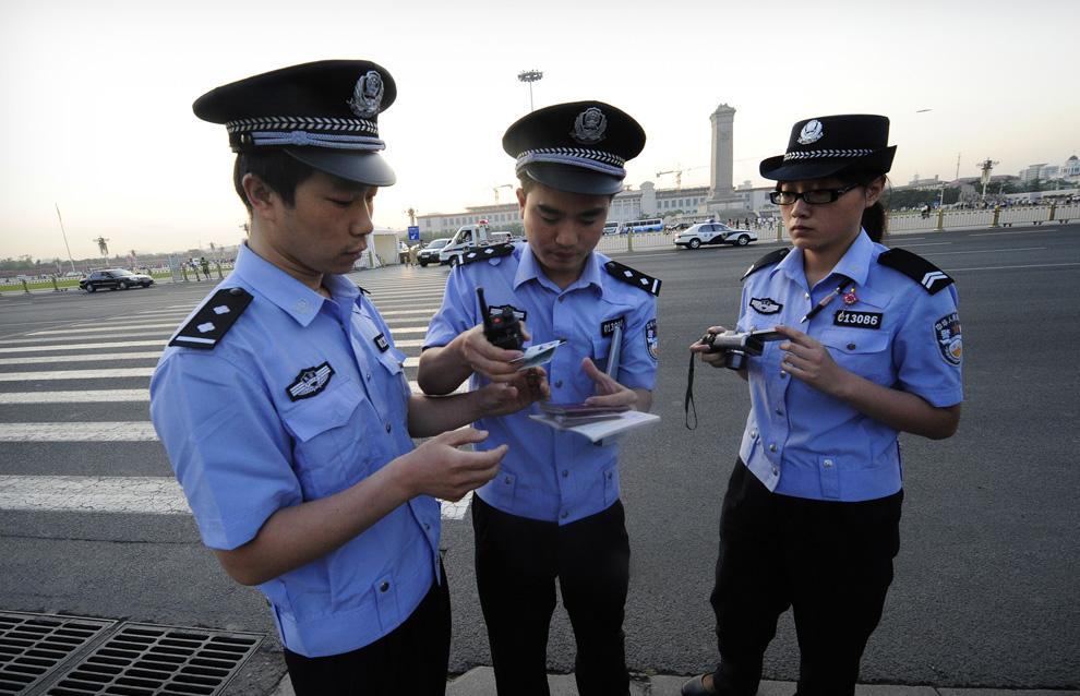 Китайские полицейские проверяют документы у иностранных журналистов, пытающихся попасть на площадь Тяньаньмэнь 4 июня 2009. Иностранным средствам массовой информации был запрещен доступ на площадь, которая находилась под усиленным наблюдением во время годовщины кровавы событий. (PETER PARKS/AFP/Getty Images)