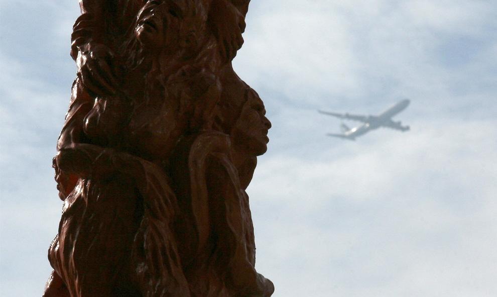 Самолет пролетает мимо «Столба позора мемориала Тяньаньмэнь» датского скульптора Йенса Галсхота (Jens Galschiot), установленного у Университета Гонконга. Фото сделано 26 мая 2009 года, за десять дней до 20-летней годовщины дня военного подавления демократических акций протеста в Пекине на площади Тяньаньмэнь в 1989 году. (REUTERS/Bobby Yip)