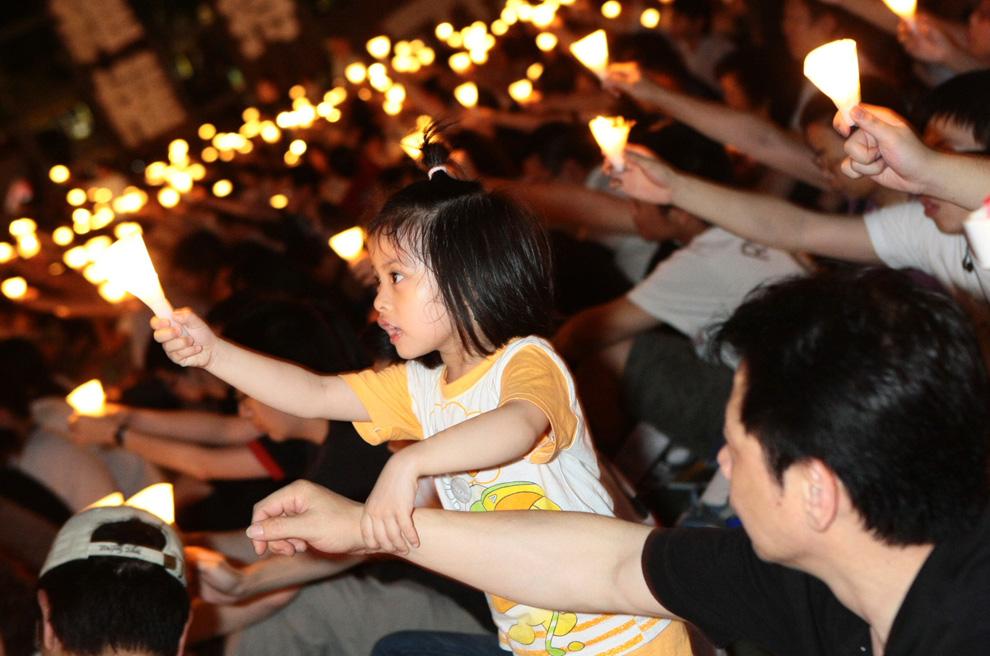 Маленькая девочка выхватила свечу у своего отца. Парк Виктория, Гонконг 4 июня 2009. Следующее поколение помнит о тех трагических событиях даже спустя 20 лет. (© Y. C. William Wang)