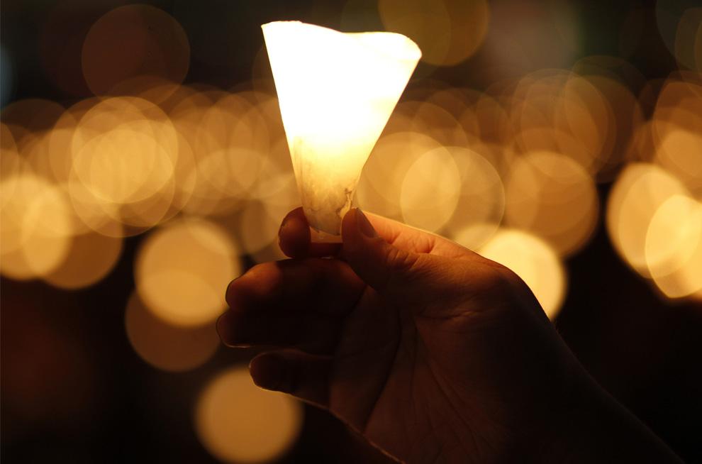Мужчина держит свечу во время многотысячного ночного бдения в гонконгском парке Виктория в четверг, 4 июня 2009. (AP Photo/Vincent Yu)