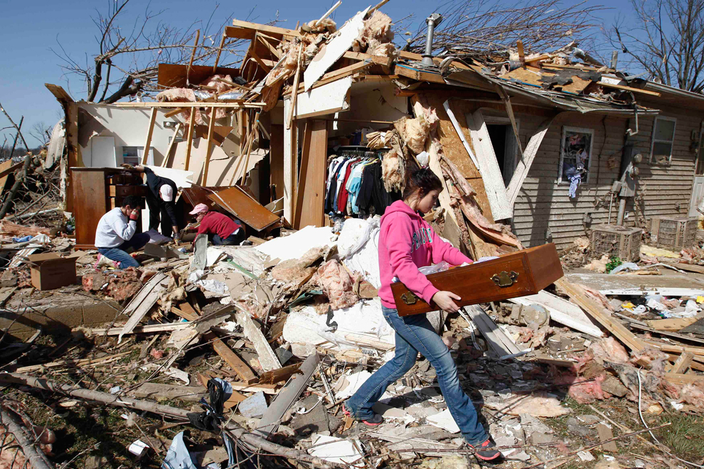 Family members salvage possessions from their destroyed house in Harrisburg, IL after the tornado.