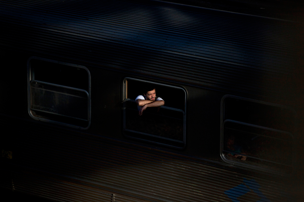A passenger peers from a train heading to the Once train station in Buenos Aires on January 28, 2013. (Natacha Pisarenko/Associated Press)