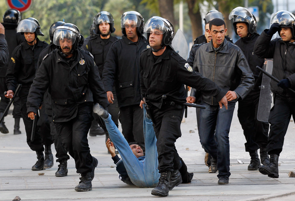 Riot police officers detain a protester during clashes in Tunis,Tunisia