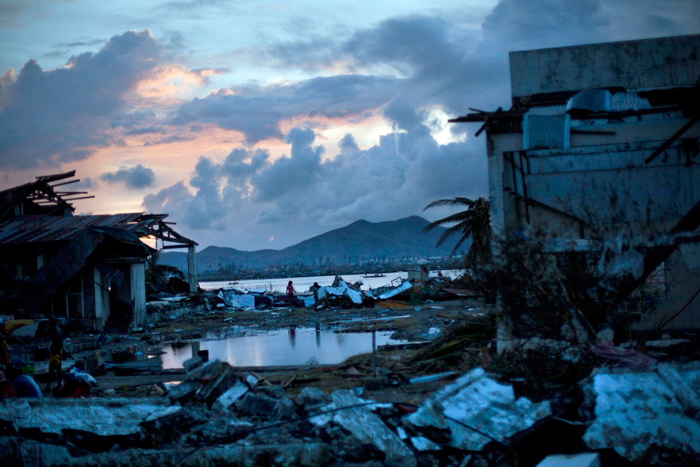 Typhoon Haiyan survivors walk through the ruins of their neighborhood on the outskirts of Tacloban, central Philippines on Nov. 13. (David Guttenfelder/Associated Press)