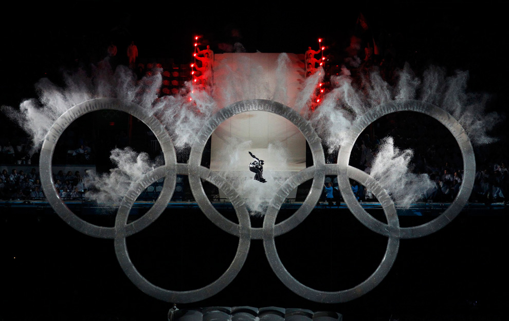 Snowboarder jumps through the Olympic rings
