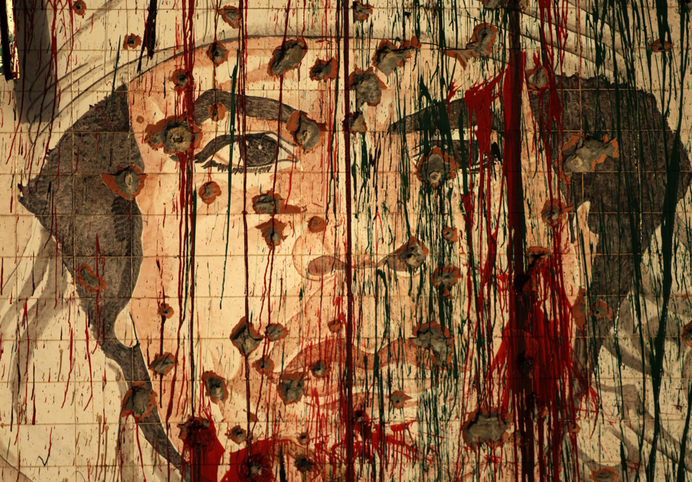 A defaced portrait of fugitive Libyan leader Moamer Kadhafi in Tripoli on Sept. 1, 2011 as the fallen strongman vowed again not to surrender in a message broadcast on the 42nd anniversary of the coup which brought him to power. (Patrick Baz/AFP/Getty Images)