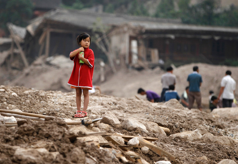 A girl stands on the debris of damaged buildings in Zhouqu County China on August 10, 2010. (REUTERS/Stringer)
