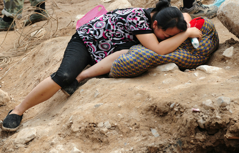 A woman cries while lying on the body of her dead child amid the rubble of landslide devastation in Zhouqu on August 11, 2010. (FREDERIC J. BROWN/AFP/Getty Images)