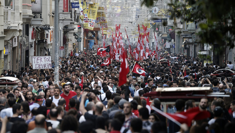 Large crowd of people walking down Istanbul city street waving the Turkish flag.