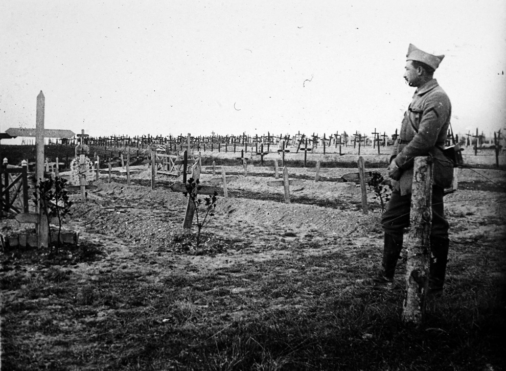 A french officer stands near a cemetery with recent graves of soldiers killed on the front lines of world war i at the saint jean sur tourbe on the
